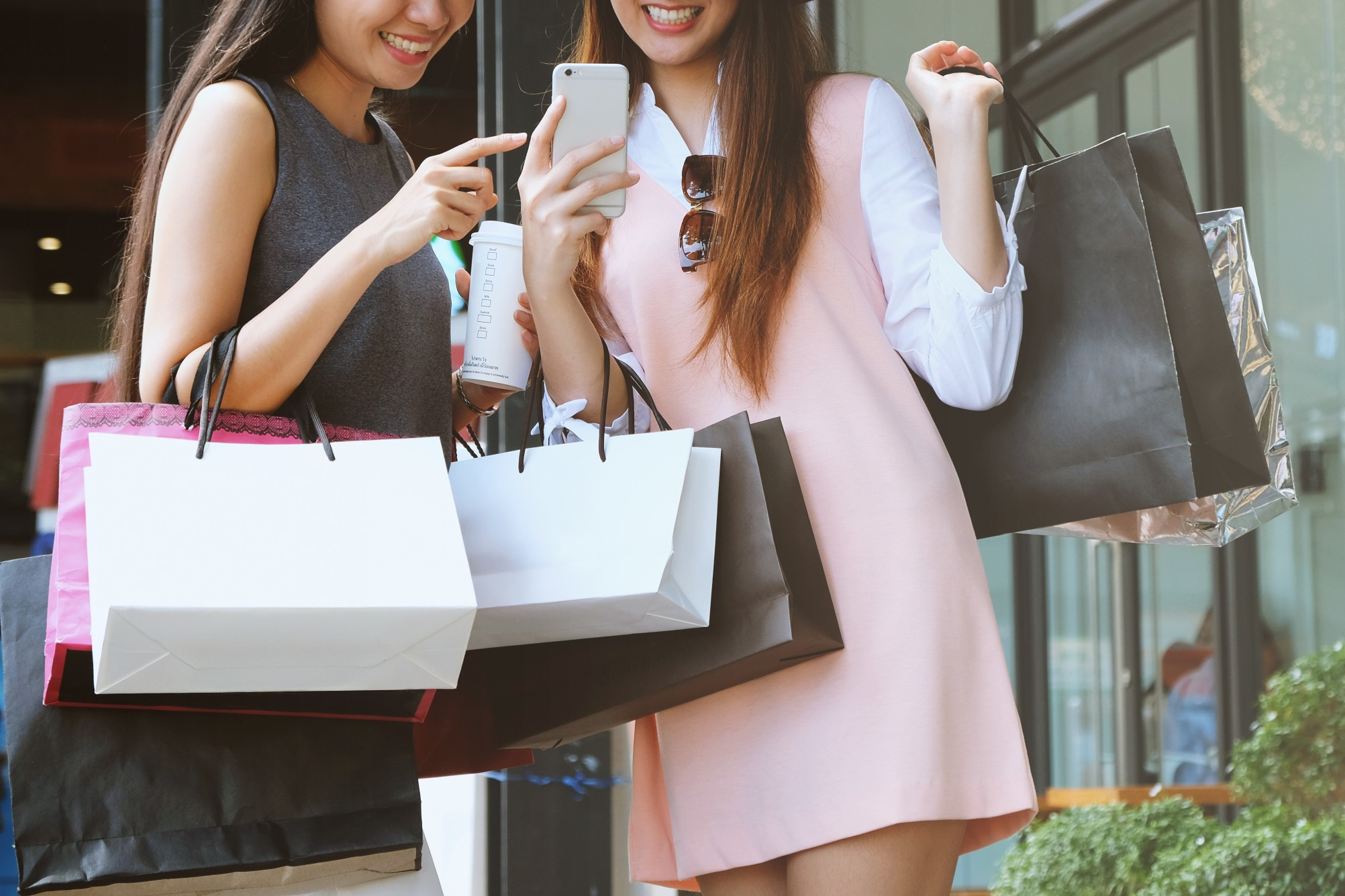 two-women-carrying-shopping-bags-while-using-smartphone-and-holding-coffee-in-the-city-street_t20_d12wRA